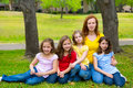 Mother teacher with daughter pupils in playground park group portrait on lawn Stock Photo