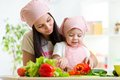 Young girl with mother preparing vegetables