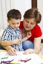 Mother teaches her son to draw with crayons Stock Photography