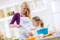 Mother teaching child how to make cakes Royalty Free Stock Photo
