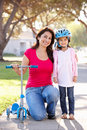 Mother Teaching Daughter To Ride Scooter Stock Photo