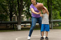 Mother teaching her son to play basketball young showing him how aim for the hoop as they practice together on a Stock Photo