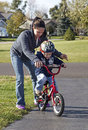 Mother teaching her son to ride a bike young fit Stock Photo