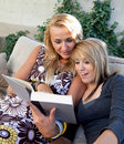 Mother and Teenage Daughter Reading Book Together Stock Image