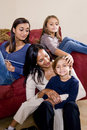 Mother and three children sitting at home together Stock Photo