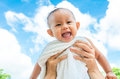 Mother throw up baby daughter with towel on blue sky background Royalty Free Stock Photo