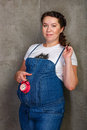 Mother to be pregnant girl in denim overalls with a clock in his hands Royalty Free Stock Images