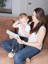 Mother and toddler son reading from wireless tablet pretty young brunette her sitting in living room interacting mobile device Royalty Free Stock Photo