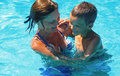 Mother train her son to swim in the pool. Royalty Free Stock Photos