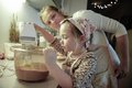 Mother tutoring her daughter in the kitchen admiring and as she is preparing dough for homemade christmas cake family values Royalty Free Stock Photography