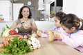 Mother and Twins Peeling Potatoes in Kitchen Royalty Free Stock Photography