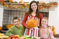 Mother and two children carving pumpkins Stock Images