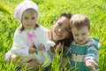 Mother with two children among green grass happy Stock Photography