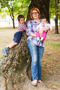 Mother with two children posing outdoors in a park leaning against a large tree Royalty Free Stock Photography