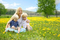 Mother and Two Children Relaxing in Flower Meadow Royalty Free Stock Photo