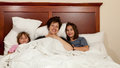 Mother and two daughters in bed Stock Photos