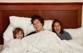 Mother and two daughters in bed Stock Photo