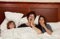 Mother and two daughters in bed yawning Royalty Free Stock Photos