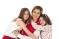 Mother and two daughters hugging in stylish fashionable outfits Royalty Free Stock Image