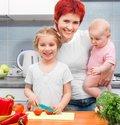 Mother with two daughters in the kitchen with vegetables Royalty Free Stock Photo
