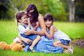 Mother and two daughters playing in grass Royalty Free Stock Images