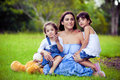 Mother and two daughters playing in grass Stock Image