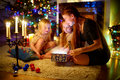 Mother and two little daughters opening a magical Christmas gift Royalty Free Stock Photo