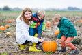 Mother and two little sons having fun on pumpkin patch. Royalty Free Stock Photo
