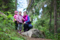 Mother with two small twins daughters walking in forest evergreen Stock Photos