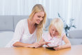 Mother using digital tablet with her daughter in the living room Royalty Free Stock Photo