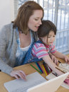Mother using laptop while daughter coloring book at table in house Royalty Free Stock Photos