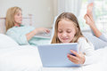 Mother using laptop while daughter using tablet pc on the bed Royalty Free Stock Photo