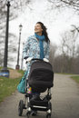 Mother walking with baby carriage in park happy young Royalty Free Stock Image