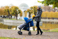 Mother walking with a baby pram in the park Royalty Free Stock Photo
