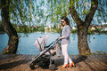 Mother walking her child near lake in city park with a beautiful pram Royalty Free Stock Photo
