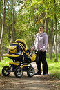 Mother walking with pram Royalty Free Stock Images