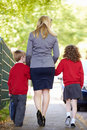 Mother walking to school with children on way to work holding hands Royalty Free Stock Photo