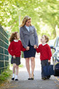 Mother walking to school with children on way to work smiling at each other whilst holding hands Stock Images