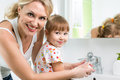 Mother washing kid hands helps baby Stock Photos