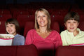 Mother Watching Film In Cinema With Two Children Stock Image