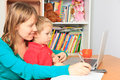 Mother woking from home wiht little son working on laptop at Stock Photo