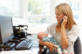 Mother working in home office with baby Royalty Free Stock Photo