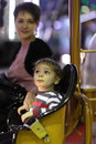 Mother woth her son on carousel at amusement park Stock Image
