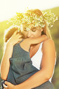 Mother in a wreath in the embrace holding baby of flowers Stock Photo