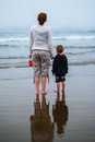 Mother and Young Child watching waves Royalty Free Stock Photo