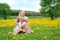 Mother and young children sitting in flower meadow laughing a happy is a of dandelion flowers with her two tickling playing Royalty Free Stock Image