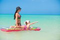 Mother with young daughter on an air mattress in the sea this image has attached release Stock Photo