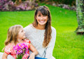 Mother and young daughter in the park relaxing on grass intimate moment Royalty Free Stock Images