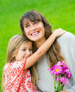 Mother and young daughter in the park relaxing on grass intimate moment Royalty Free Stock Photos