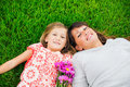 Mother and young daughter in the park relaxing on grass intimate moment Royalty Free Stock Photo